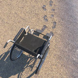 Empty wheelchair on a beach of sand with footprints Royalty Free Stock Photography