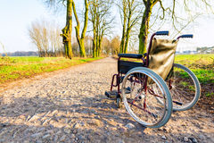 Empty wheelchair on the field road at sunset Royalty Free Stock Photography
