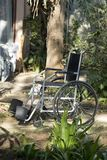 Empty Wheelchair in Garden - Vertical royalty free stock photography