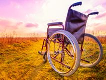 Empty wheelchair on the meadow at sunset. Miracle concept. Healed person raised and went away stock photos