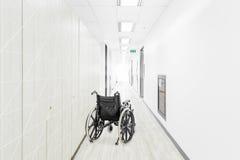 Empty wheelchair parked in hospital hallway.  Stock Photos