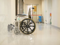 Empty wheelchair parked in hospital pathway Royalty Free Stock Photo