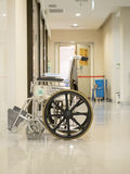 Empty wheelchair parked in hospital pathway Royalty Free Stock Photos