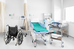 Empty wheelchair parked in hospital room with beds and comfortab Royalty Free Stock Photo