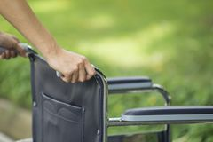 Empty wheelchair pushed by nurse`s hands Stock Image