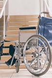 Empty wheelchair and stairs. Disabled accessibility reality. Wheelchair Stock Photos