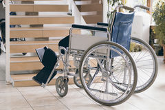 Empty wheelchair and stairs. Disabled accessibility reality. Wheelchair Royalty Free Stock Images