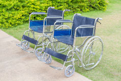 Empty wheelchairs service in the public park. Two empty wheelchairs service in the public park Royalty Free Stock Images