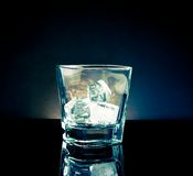 Empty whiskey glass with ice and light tint blue disco on black background Stock Images