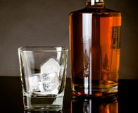 Empty whiskey glass with ice near bottle on black background Stock Image
