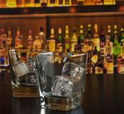 Empty whiskey glasses with ice on bar table Stock Images