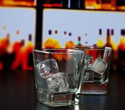 Empty whiskey glasses with ice on bar table. Lounge bar concept Stock Image