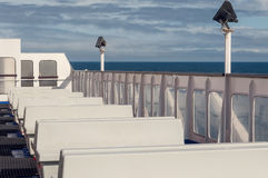 Empty white benches on ferry boat in open sea in sunny weather. White seats or benches on ferry boat with visible horizon and blue water Royalty Free Stock Images