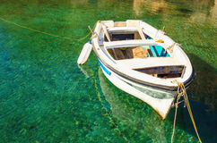 Empty white boat floating in clear water. Greece Stock Photo