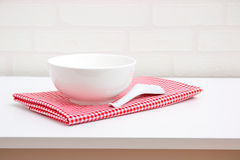Empty white bowl and spoon on red tablecloth Stock Photos