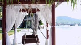 Empty white canopy swing by the beach next to the palm tree. 3840x2160. Empty white canopy swing or patio swing by the beach next to the palm tree stock video footage
