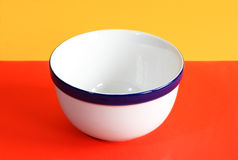 Empty white ceramic bowl. On the red-yellow background royalty free stock image