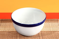 Empty white ceramic bowl. On the bamboo desk and red-yellow background royalty free stock photo