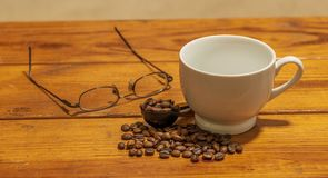 Empty white ceramic coffee cup next to eye glasses, small pile of roasted coffee beans and measuring spoon atop wooden coffee tabl stock photos