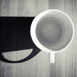 Empty white ceramic coffee cup on wooden table. Background with strong dark shadow Royalty Free Stock Photography