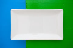 Empty white ceramic dish on over blue and green background, rect Stock Images