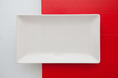 Empty white ceramic dish on over red and white background, recta Royalty Free Stock Photos