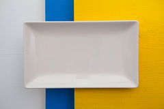 Empty white ceramic dish on over white, blue and yellow  wooden Royalty Free Stock Photos