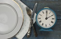 empty white ceramic dish and vintage silverware on wooden background royalty free stock image