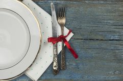 empty white ceramic dish and vintage silverware on wooden background stock image