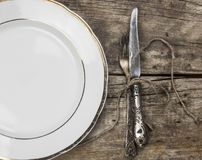 empty white ceramic dish and vintage silverware on wooden background stock photo