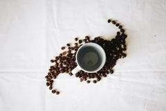Empty White Ceramic Mug Surrounded by Coffee Grounds royalty free stock photography