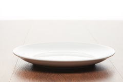 Empty white ceramic plate on bright light brown wooden table Royalty Free Stock Photos