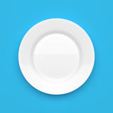 Empty white ceramic round plate on blue. Background Royalty Free Stock Photos