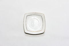 Empty white ceramic saucer on a gray background. Flat lay, top view Stock Images