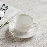 Empty white ceramic tea cup, book and glasses Stock Photos