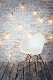 Empty white chair against the backdrop of a brick wall with a garland of light bulbs. Royalty Free Stock Photo
