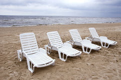 Empty white chairs near sea on beach sand Stock Image
