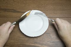 Empty plate with hands holding knife and fork. Empty white china plate with hands holding pewter knife and fork on wooden boards with copy space Stock Photos