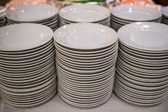A stack of white plates. Empty white clean plates. Row of stack for party or event buffet at hotel restaurant Stock Image