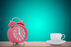 Empty white Coffee cup with Alarm Clock on the wooden against th. E green background stock photography