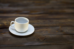 Empty white coffee cup and saucer. On a wooden background Royalty Free Stock Images