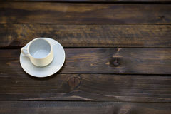 Empty white coffee cup and saucer. On a wooden background Royalty Free Stock Photo