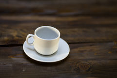 Empty white coffee cup and saucer. On a wooden background Royalty Free Stock Image