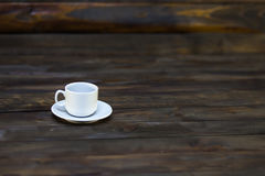 Empty white coffee cup and saucer. On a wooden background Royalty Free Stock Photography