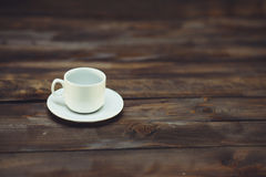 Empty white coffee cup and saucer. On a wooden background Stock Images
