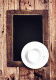 Empty white  Coffee cup on  vintage blackboard. Blank slate chal Royalty Free Stock Photo