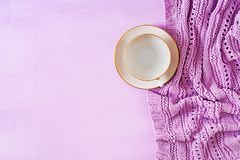 Empty white coffee cup on violet background, close up photo knitted sweater. With mug, winter morning concept. Top view. Flat lay royalty free stock photo