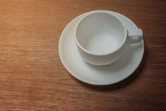 Coffee cup. Empty white coffee cup on wooden table Royalty Free Stock Photo