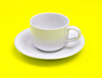 Empty white coffee or tea cup on vibrant yellow color background Stock Photo