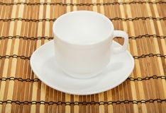Empty white cup on a bamboo napkin Royalty Free Stock Photo